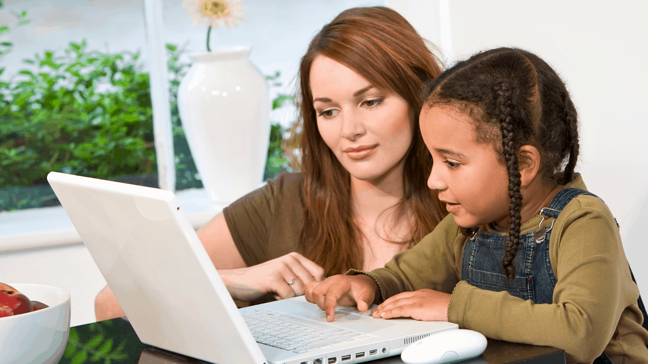 A mom being a helicopter parent and closely supervising her daughter doing her homework on the laptop.