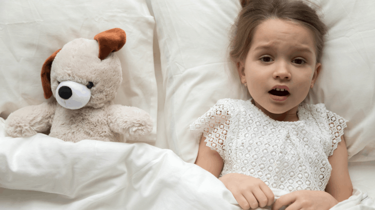 A frightened girl in bed having been woken by a night terror