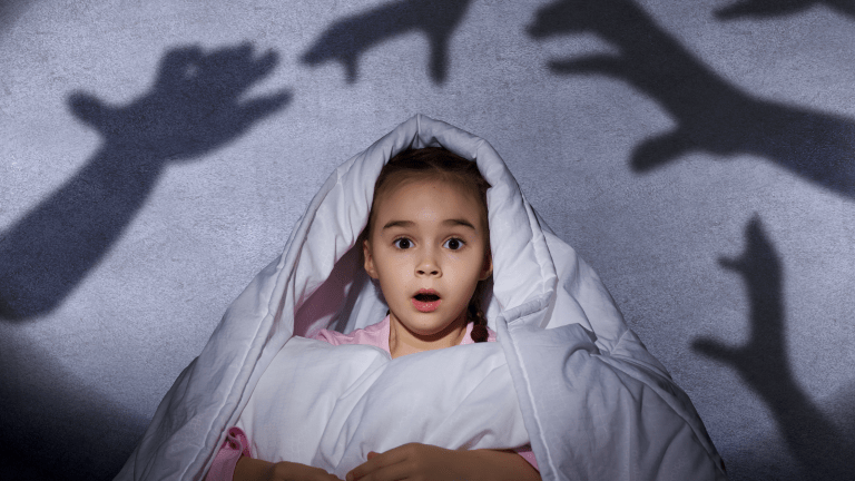 A frightened child watching shadows in bed, having been woken by a night terror