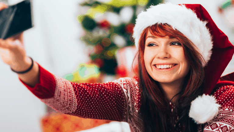 A girl at an online Christmas party wearing a Christmas jumper and a Christmas hat, chatting to her friends on her phone.