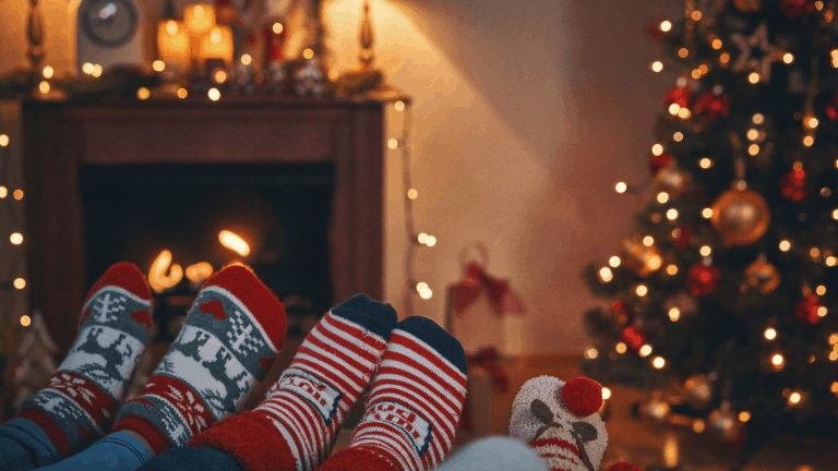 A family having a cosy Christmas at home due to Covid restrictions. Sitting in front of the fire and Christmas tree with Christmas socks on.