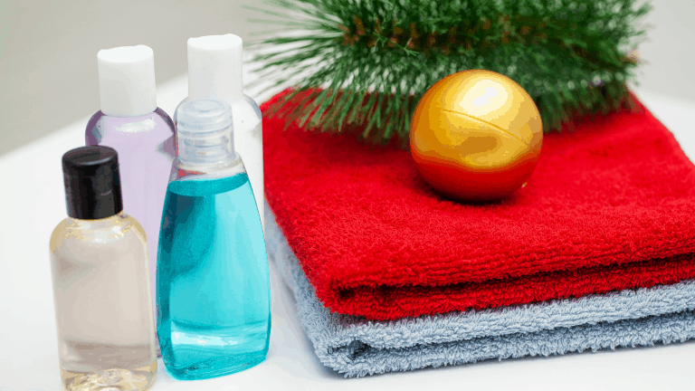 Hand soap, hand sanitizer and towels for a Covid-safe Christmas with a bauble and pine tree branch.