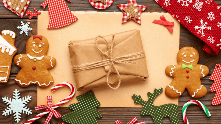 Homemade Christmas gifts – gingerbread men, candy canes and decorations wrapped in brown paper and string.