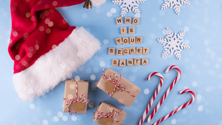 A flatlay with a Santa hat, presents, candy canes and snowflakes and wooden letter tiles spelling out, 'Who is your secret Santa?