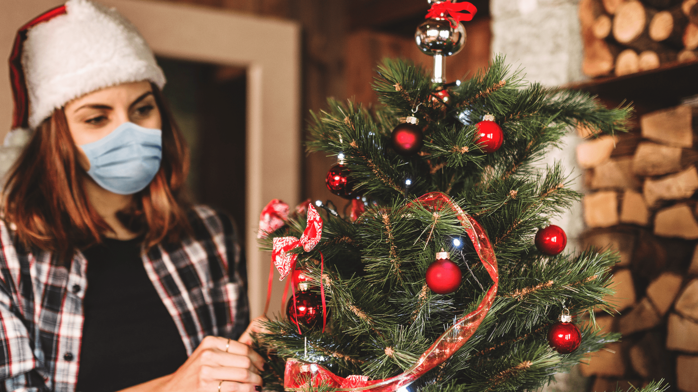 Woman with face mask and Santa hat on decorating her Christmas tree.