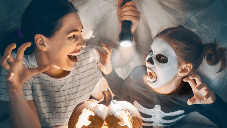 Mum and daughter telling ghost stories at Halloween by torchlight under a duvet.