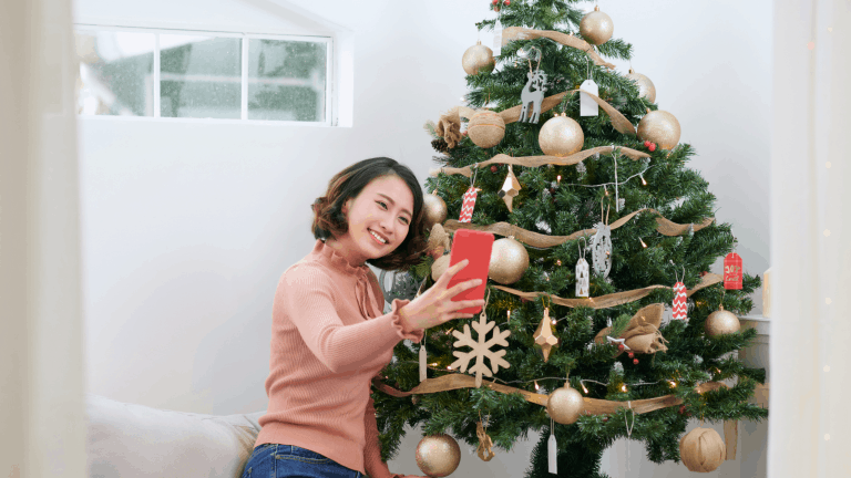 A woman joining her friends in a Christmas tree decorating party on Zoom.