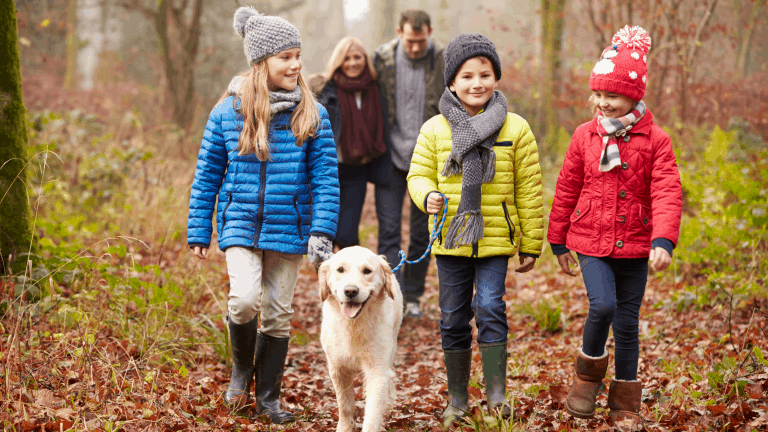 A family out for a walk in the woods with their dog.