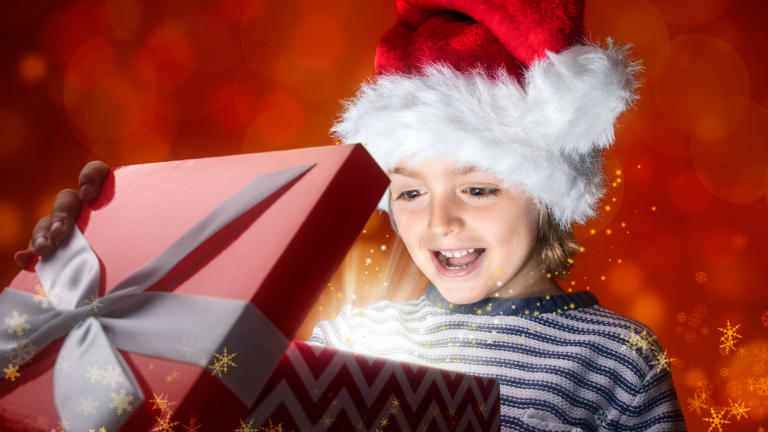 Family Christmas traditions: a girl wearing a Santa hat opening a Christmas Eve box which is glowing inside.