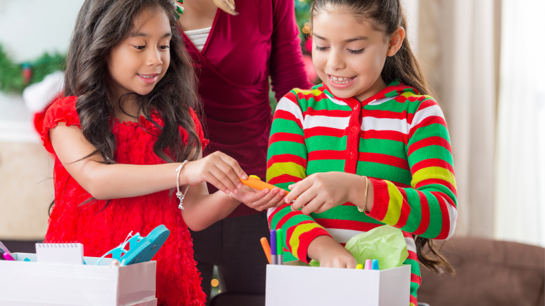 Family Christmas traditions: Two girls filling shoeboxes with Christmas gifts for disadvantaged children, ready to be sent to the Samaritan's Purse Operation Christmas Child Appeal.
