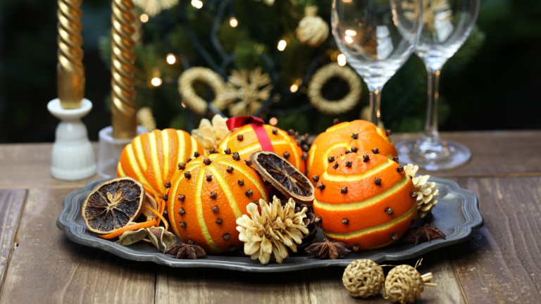Family Christmas traditions: a tray full of orange pomanders – oranges with patterns cut into the peel and decorated with cloves and ribbons.