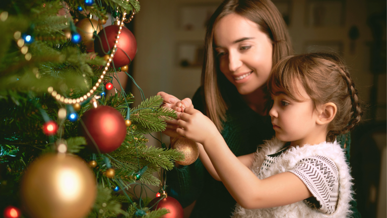 Family Christmas traditions: A mother and daughter putting decorations on the Christmas tree.