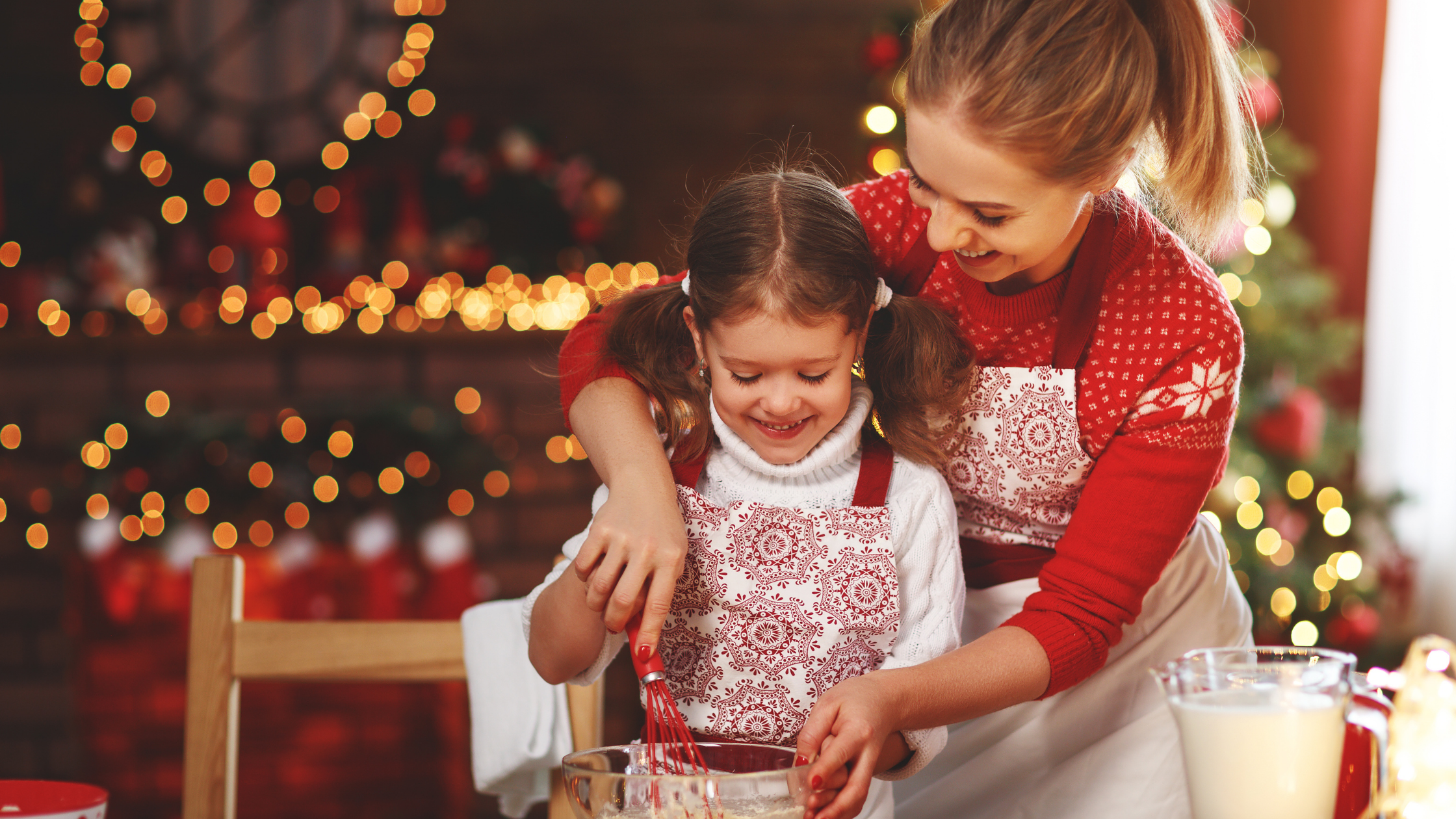 Family Christmas traditions: a mother baking Christmas goody with her daughter in front of a Christmas tree.
