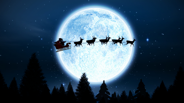 Family Christmas traditions: Santa and his reindeer flying across the night sky in front of the moon and over some trees.