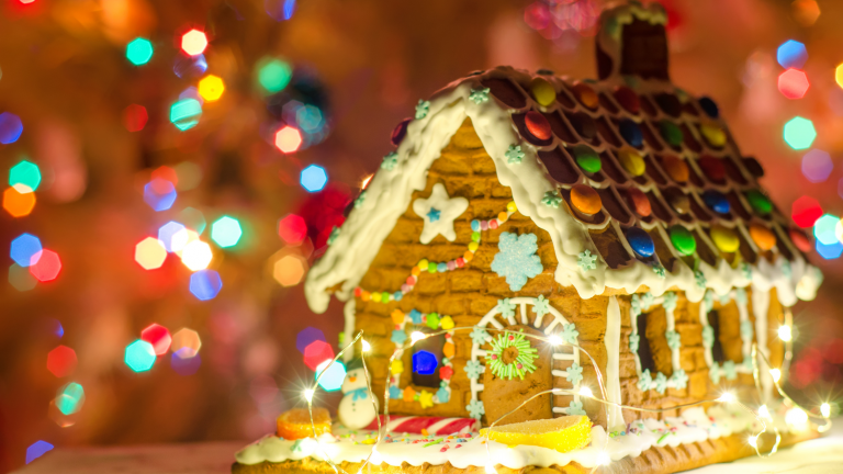 Family Christmas traditions: A gingerbread house, decorated with sweets and icing and lit with battery-operated fairy lights, positioned in front of some Christmas lights.