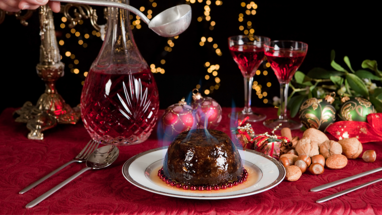 Family Christmas traditions: Someone pouring brandy onto a lit Christmas pudding with a ladle.
