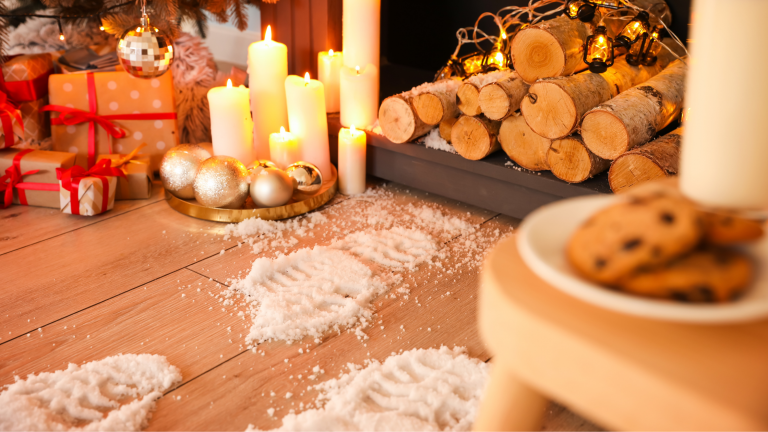 Family Christmas traditions: Santa's snowy footprints by a fireside, next to presents, lit candles and some milk and cookies.