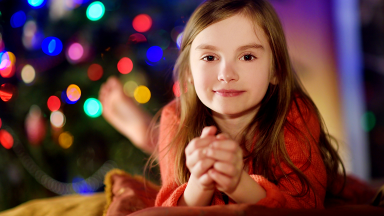 Family Christmas traditions: A girl lying in front of a Christmas tree watching a Christmas movie.