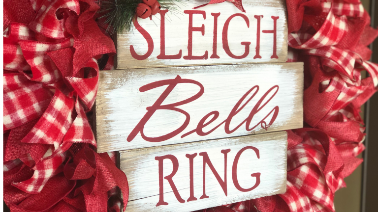 """Family Christmas traditions: A sign surrounded by Christmas ribbons which reads, """"Sleigh bells ring."""""""