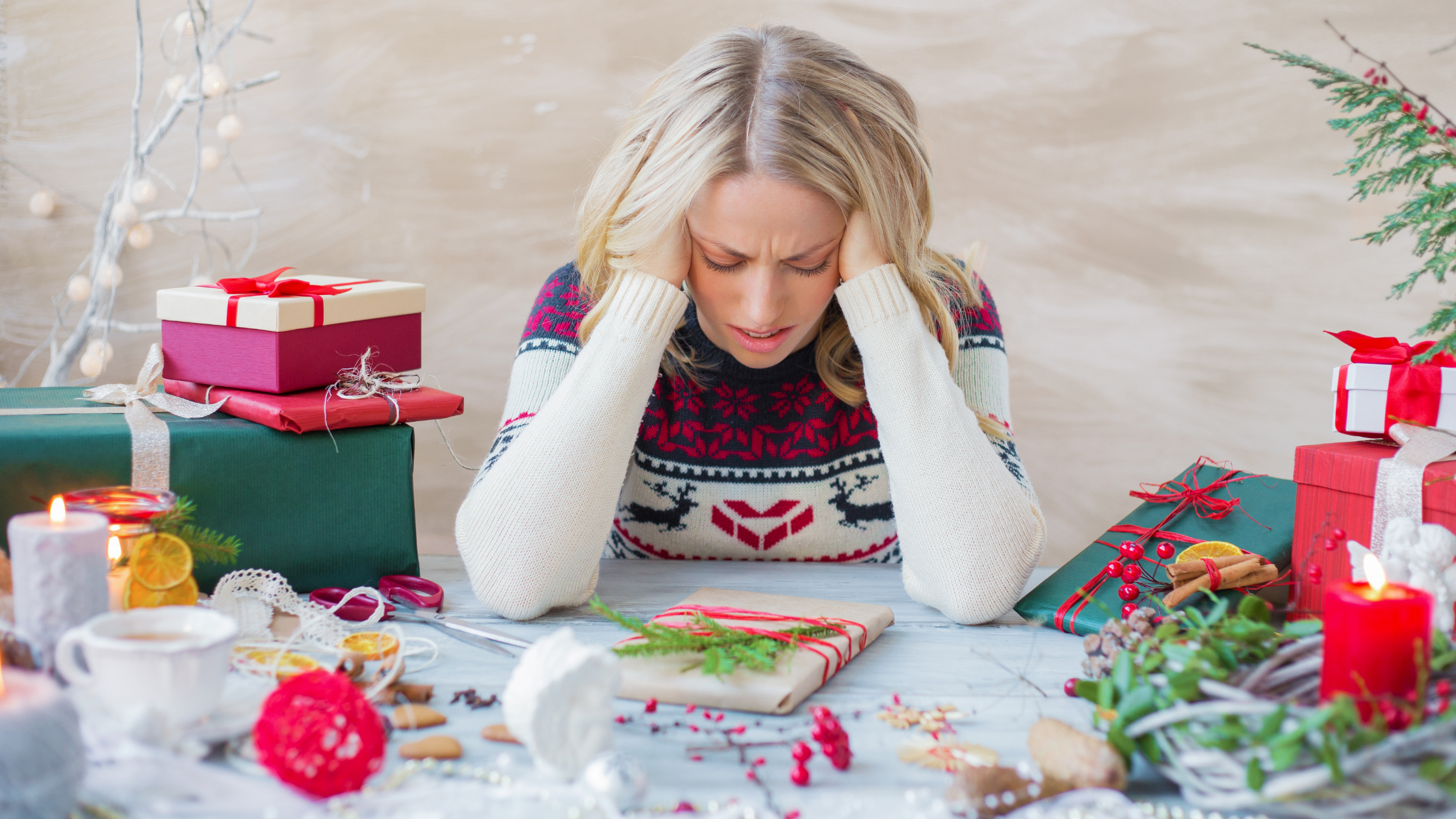 Woman stressing about Christmas with her head in her hands as she attempts to wrap Christmas gifts.