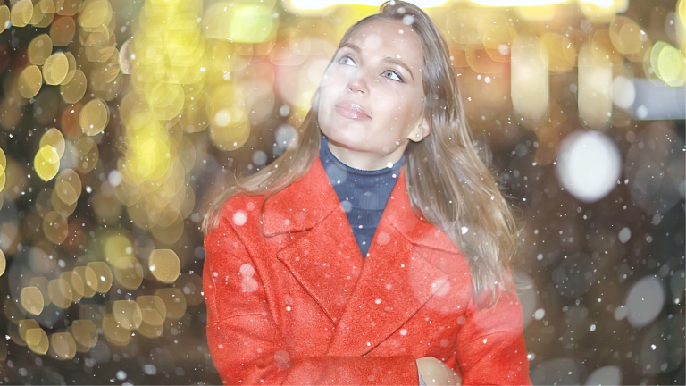 A woman in a red coat out for a walk and watching the snow falling in order reduce anxiety to stop stressing over Christmas.