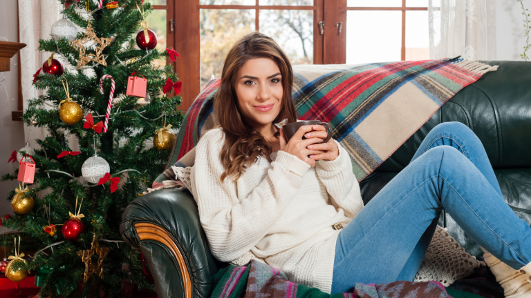 A woman sitting on a cosy blanket on sofa with her feet up, next to a Christmas tree with a mug in her hands. Looking relaxed and not stressing about Chirstmas.