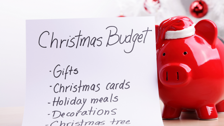 A Christmas budget list next to a red piggy bank with a Santa hat on it.