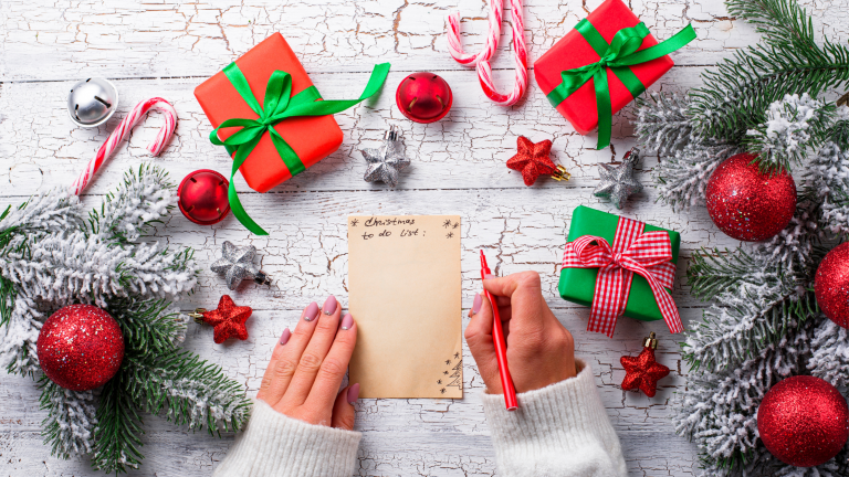 A woman writing a Christmas to-do list surrounded by gifts and Christmas decorations.