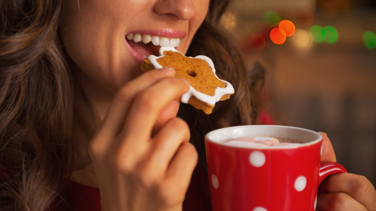 A woman eating a Christmas cookie and drinking a hot chocolate with marshmallows on the top.