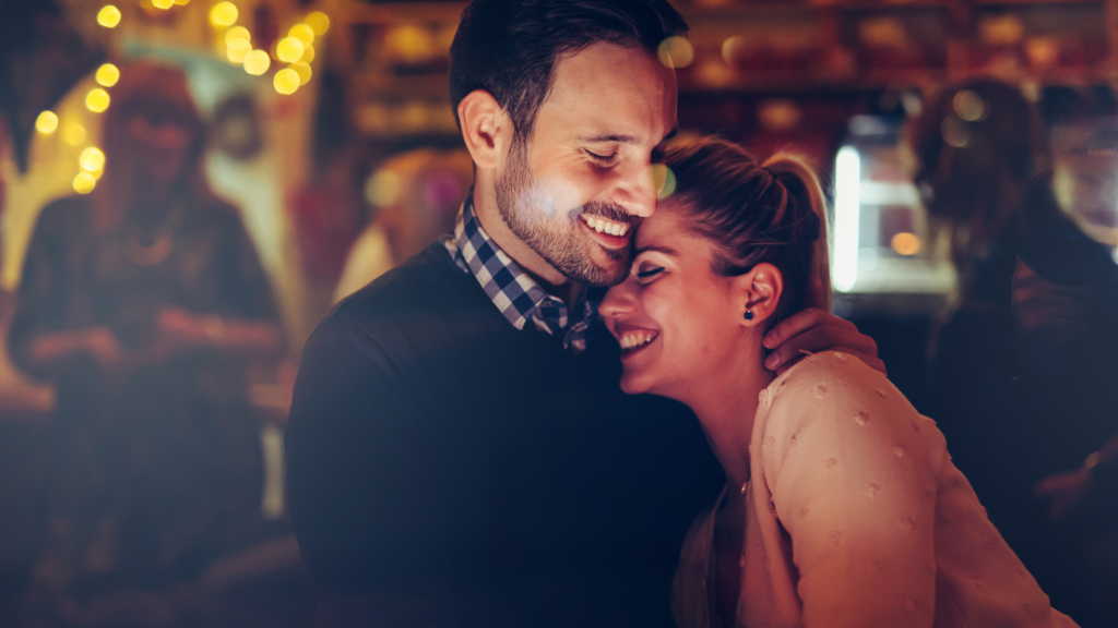 A couple out on a date night and having a hug. A secret to a happy family is to prioritise your partner.