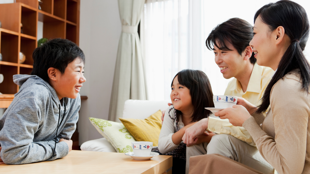 A happy family sitting together around a coffee table chatting while drinking tea – mum, dad, a son and daughter.
