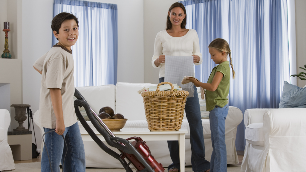 A daughter helps her mother fold laundry next to a washing basket in a living room, while the son vacuums nearly.