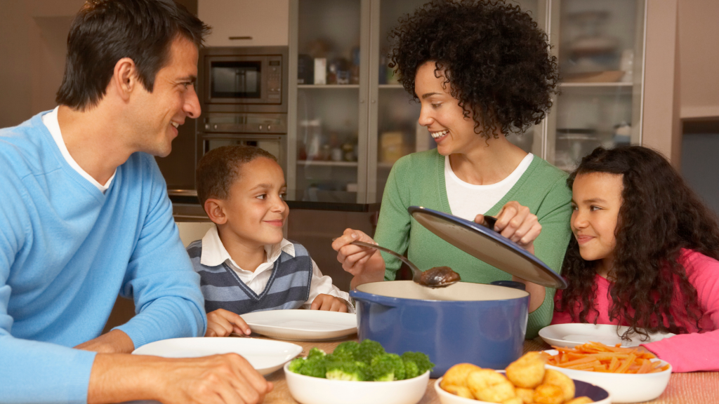 A happy family eating dinner together: a mum, dad, son and daughter. Mum is serving a stew from a casserole dish.