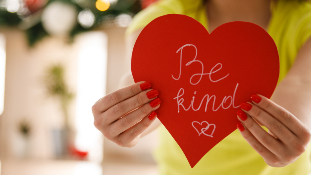A woman in a yellow top holding a red heart out in front of her which has, 'Be kind' written on it with two little hearts, to show that kindness is key to a happy family.