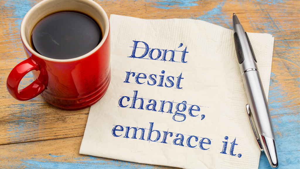 A red coffee mug and a pen on a wooden table next to a napkin that has the words, 'Don't resist change, embrace it,' printed on it.