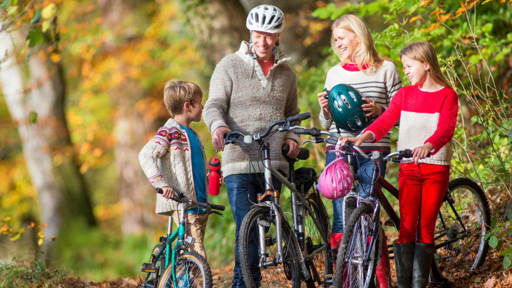 A happy family out on a bike ride – a mum, dad, son and daughter standing with bikes in the countryside chatting. Mum is holding a bike helmet and the son a water bottle.