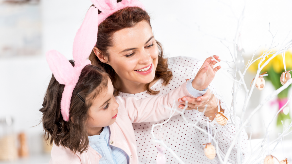 A mother and young daughter decorating a white branch with easter eggs.