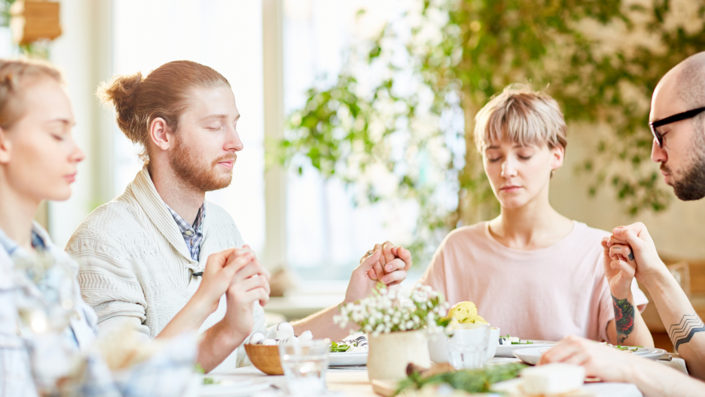 A family gathered around a table, holding hands with their eyes shut as they sit in grateful thought – to show how developing a gratitude practice can help maintain a happy family.
