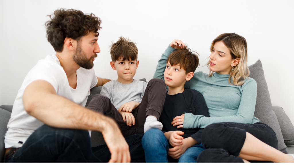 A family sitting together on a sofa having a discussion – mum, dad and two boys.