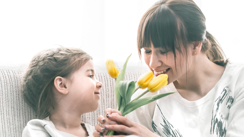 A young girl giving her mum a bunch of daffodils. Her mum is smiling, closing her eyes and smelling them. This shows how small gestures and acts of kindness can help to keep a family happy.