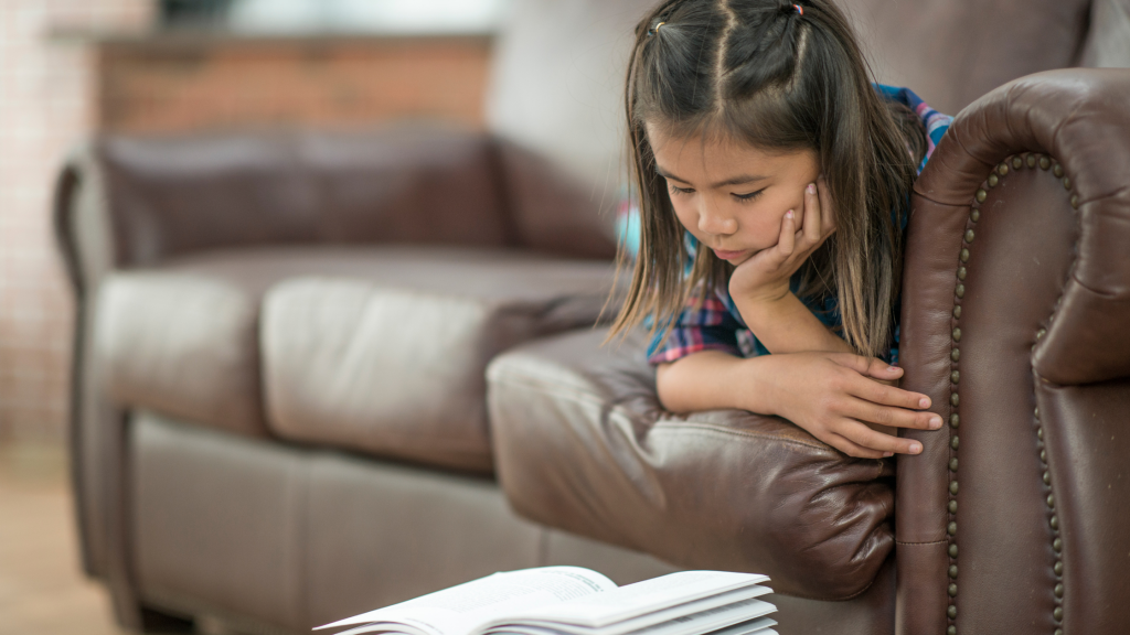 A young girl lying on a brown sofa, with her head propped on her hand and reading a book.