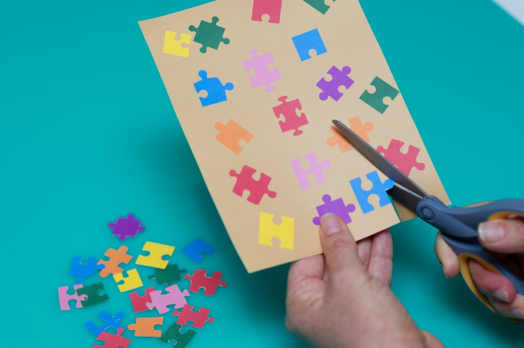 Cutting out puzzle pieces to stick on Father's Day card