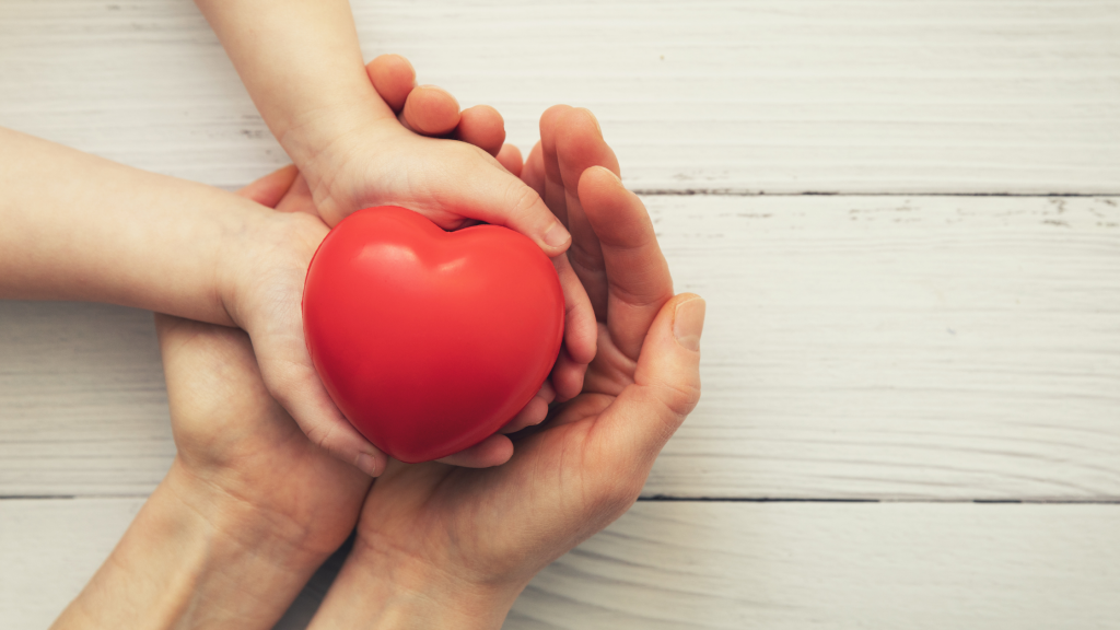 Adult and child hands holding a red heart to signify empathy