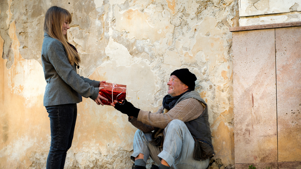 girl giving gift to homeless man  - showing empathy
