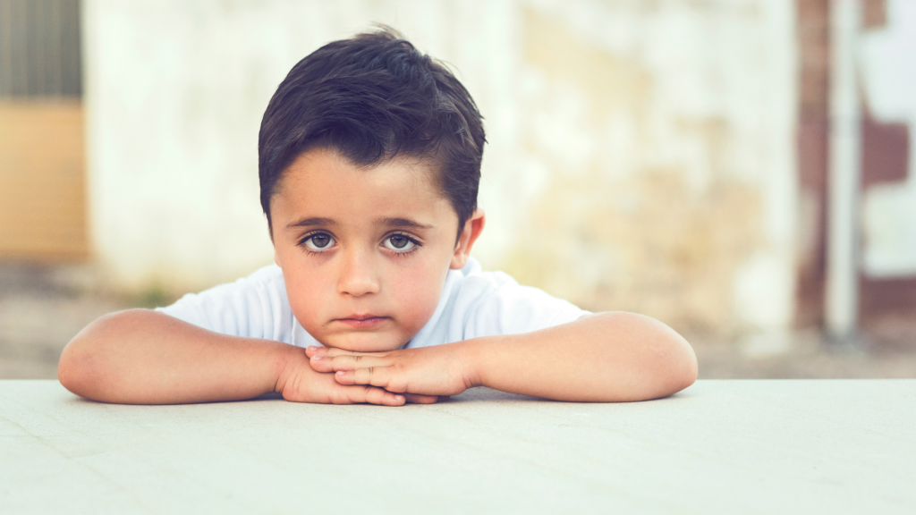 Boy with his head on his hands, looking sad and with low self-esteem