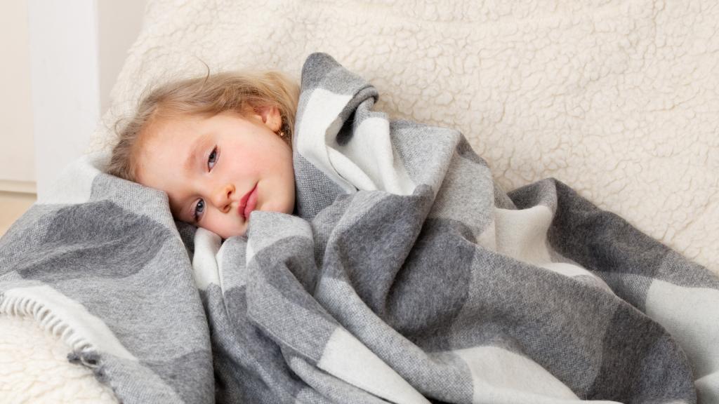 A sick gilr lying on a sofa under a blanket