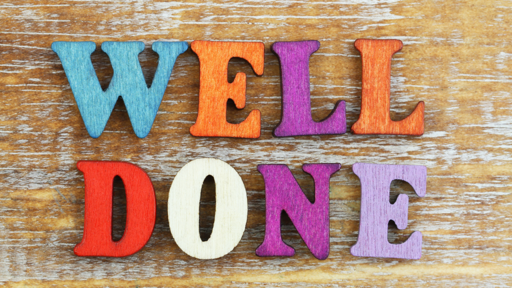 The words 'well done' spelt out in colourful wooden letters