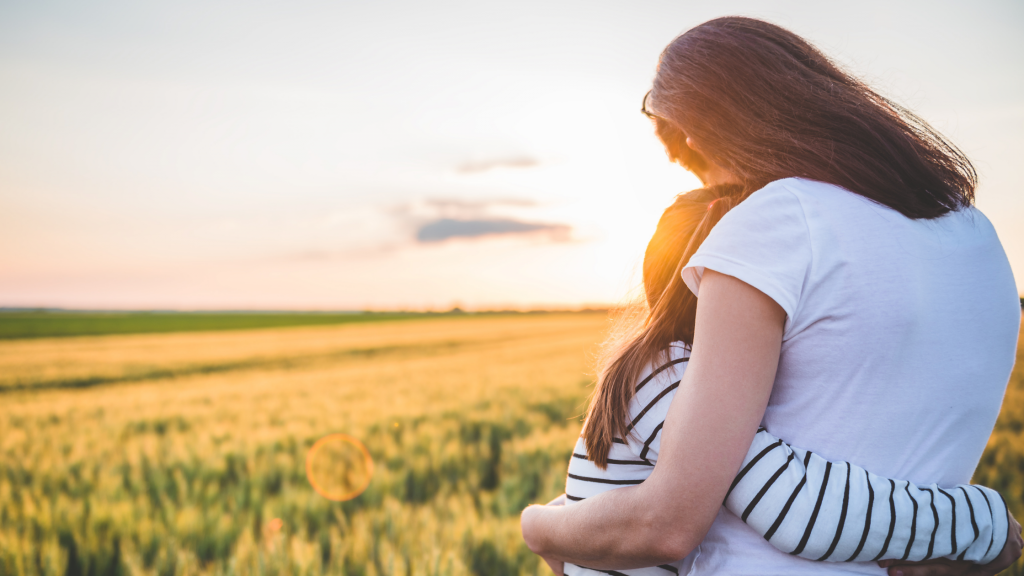 Mother hugging her daughter while watching a sunset over a field.