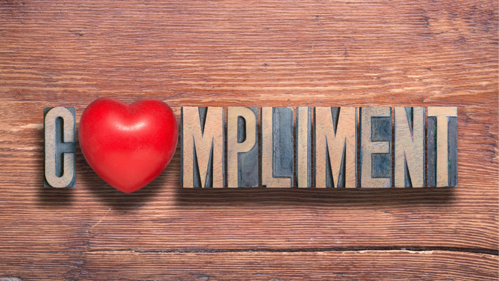 The word 'compliment written in wooden letters with a red heart for the 'o'.